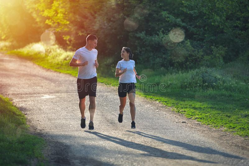 Ungdomarsom joggar och övar i natur, i varmt ljus för morgonsoluppgång royaltyfri fotografi