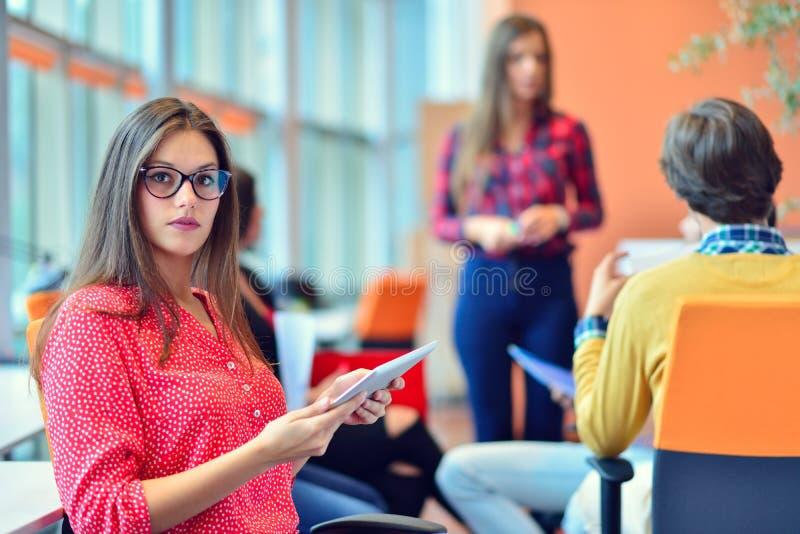Ungdomarsom möter den digitala minnestavlan i startup kontor royaltyfri foto