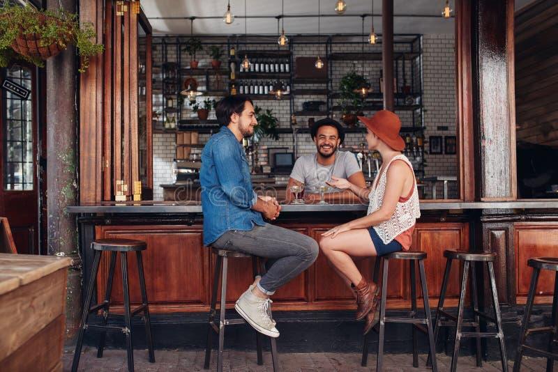 Ungdomarsom sitter i ett kafé och ett samtal arkivbild