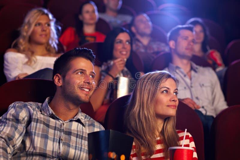 Ungdomarsom sitter på filmbiografen royaltyfria bilder