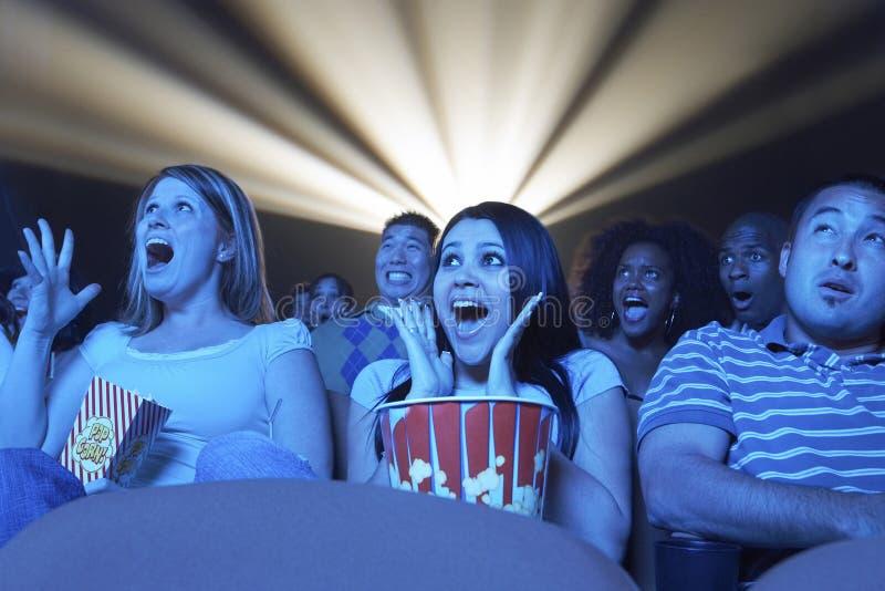 Ungdomarsom skriker, medan hålla ögonen på fasafilm i teater royaltyfri fotografi