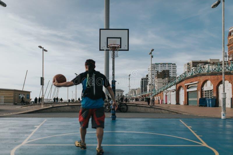 Ungdomarsom spelar basket i gatorna i Brighton, UK arkivbilder