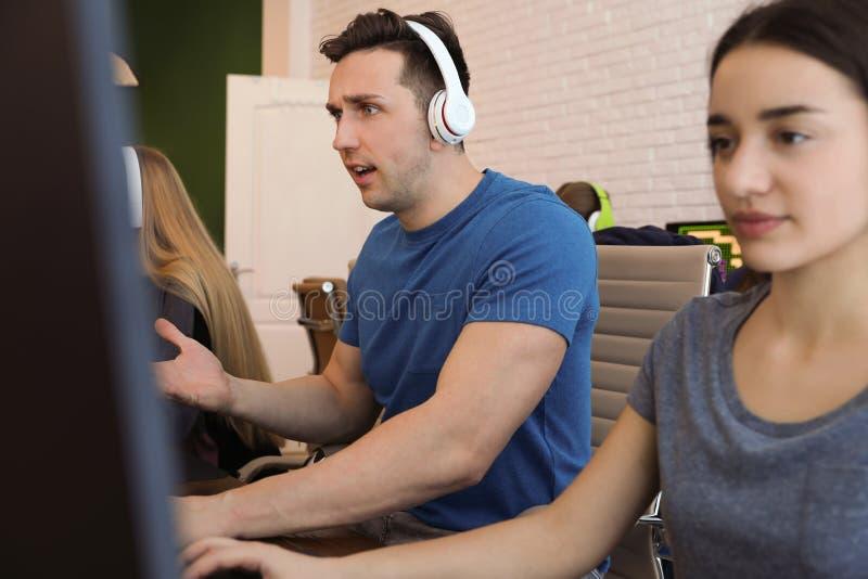 Ungdomarsom spelar videospel p? datorer Esports turnering arkivbild