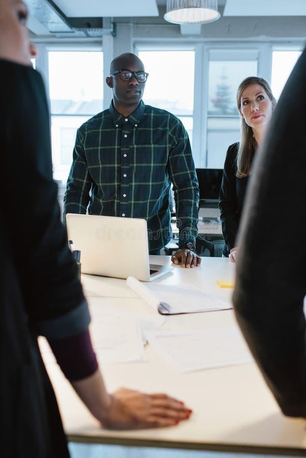 Ungdomarsom står på en tabell som diskuterar arbete royaltyfria foton