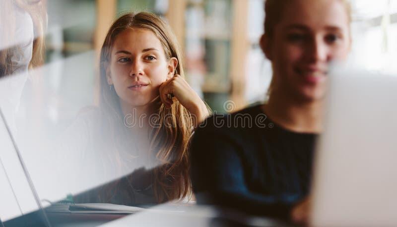Ungdomarsom studerar i universitetklassrum royaltyfri foto