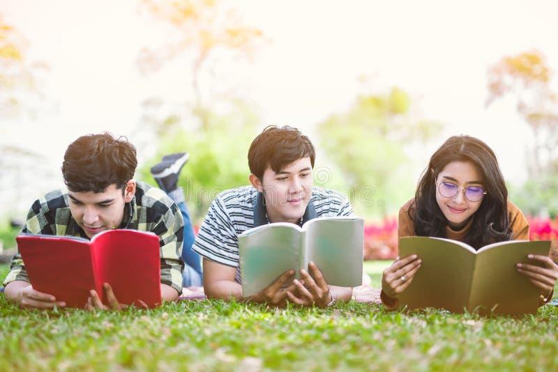 Ungdomarsom studerar läseboken parkerar in utbildningsstudie, vid läst arkivfoton