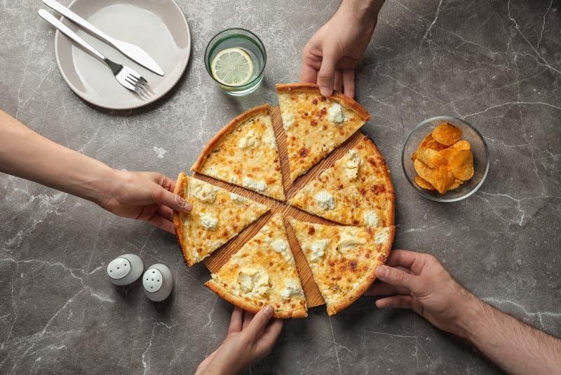 Ungdomarsom tar skivor av smaklig ostpizza på tabellen royaltyfri foto