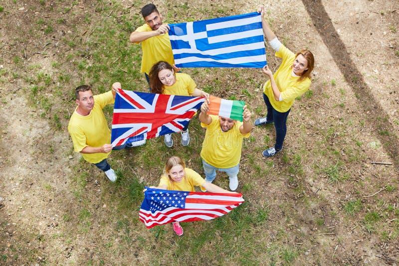 Ungdomarstår med olika nationsflaggor arkivbild