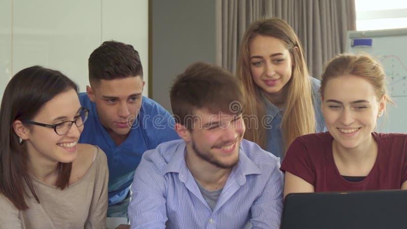 Ungdomarvisar upp deras tummar på kontoret royaltyfri foto