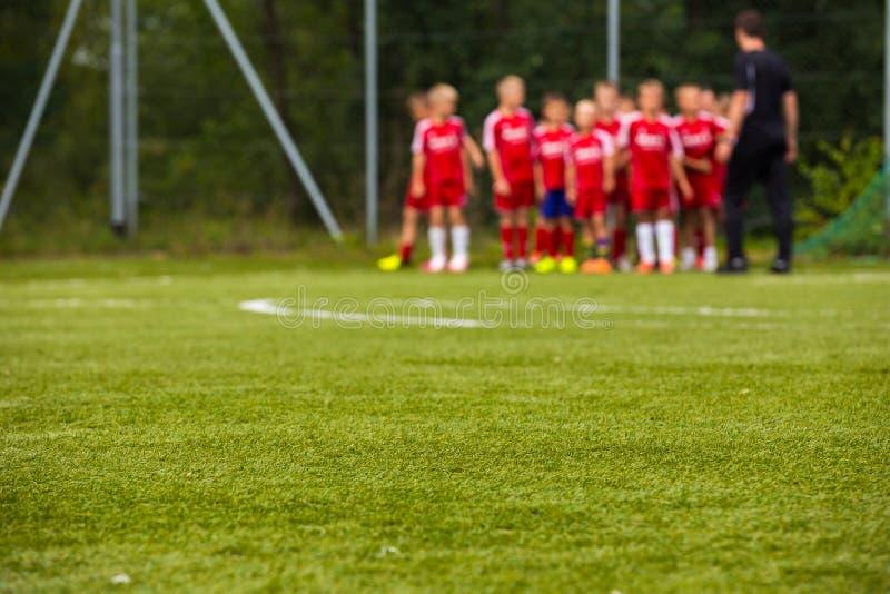 Ungdomfotbollslag med lagledaren på graden; Suddig fotbollbakgrund fotografering för bildbyråer