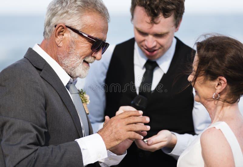 Ungdomligt mogna par som får att gifta sig på stranden royaltyfri fotografi