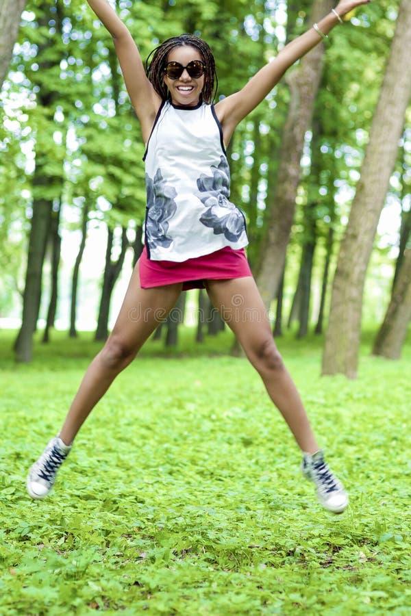 Ungdomlivsstilbegrepp Afrikansk amerikantonåringflicka med trevliga Dreadlocks som hoppar med positivt uttryck royaltyfria bilder