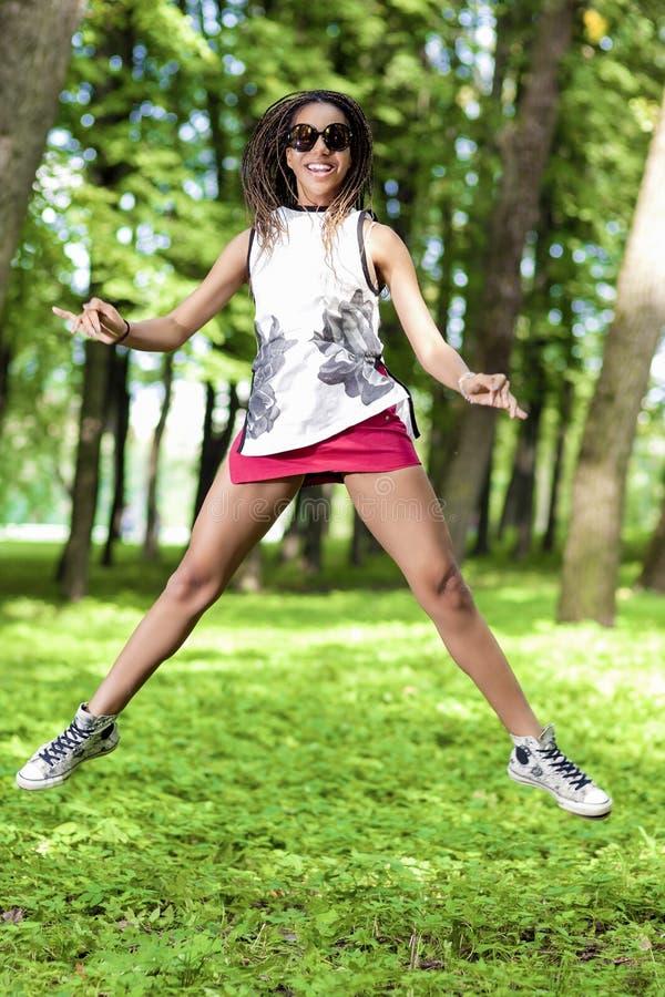 Ungdomlivsstilbegrepp Afrikansk amerikantonåringflicka med trevliga Dreadlocks som hoppar med utsträckta händer i grön skog fotografering för bildbyråer