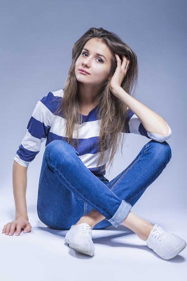 Ungdomlivsstilidéer Caucasian brunettflickasammanträde på golv arkivfoto