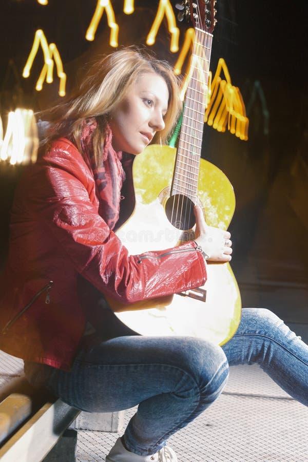 Ungdomlivsstilidéer och begrepp Caucasian blond kvinna som spelar gitarren utomhus på natten arkivfoton