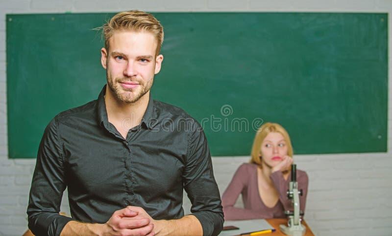 Ungdommentoring Mannen ansade v?l den attraktiva l?raren framme av klassrumet Hems?kt med kunskap L?rare av henne arkivfoton