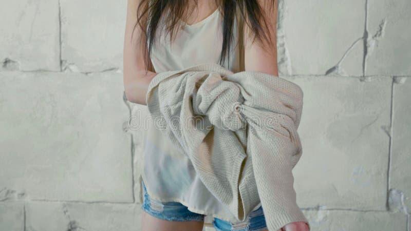 Ungdommodellen klär upp tröjan över den vita stenväggen fotografering för bildbyråer
