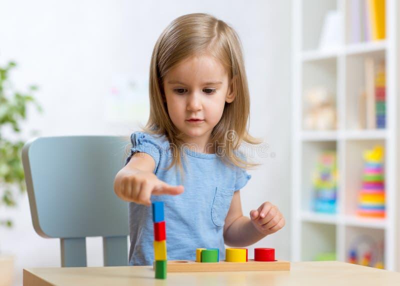 Unge för litet barn som spelar med byggnadskvarter royaltyfria bilder