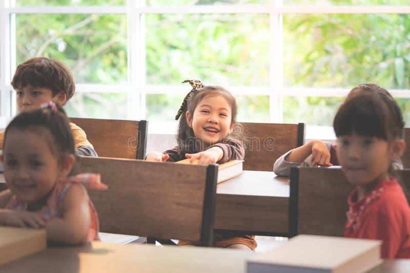 Unge för tillbaka rum som skrattar i lycklig klassrumskola royaltyfri foto