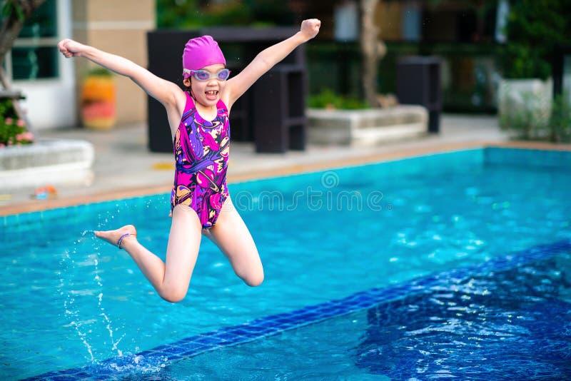 Unge flicka och att hoppa in i simbassäng med gyckel och lycka royaltyfri fotografi