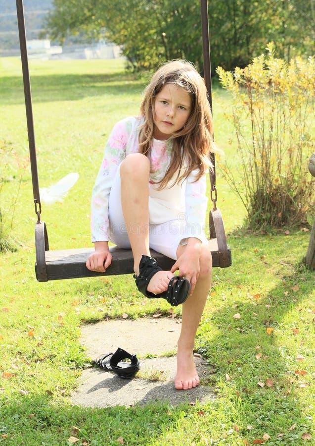 Unge - flicka som sätter på skor på gunga royaltyfria foton