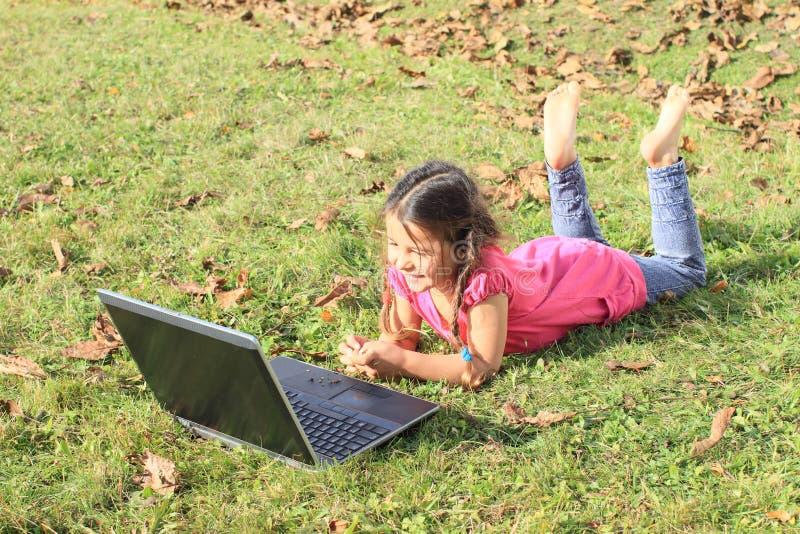 Unge - flicka som spelar med anteckningsboken royaltyfri bild