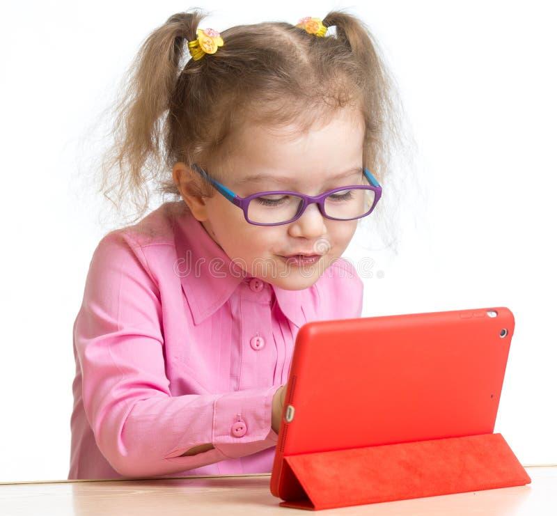 Unge i exponeringsglas som ser den mini- minnestavlaPCskärmen på tabellen royaltyfria bilder