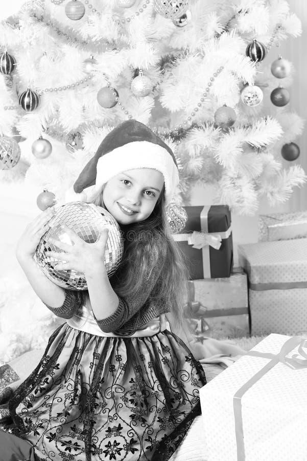 Unge i jultomtenhatt vid gåvor Flicka med att le framsidan royaltyfria foton