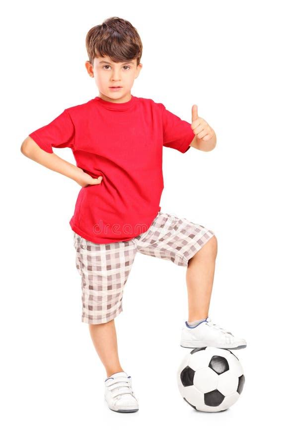 Unge med en fotboll under hans fot som ger upp en tumme arkivfoto