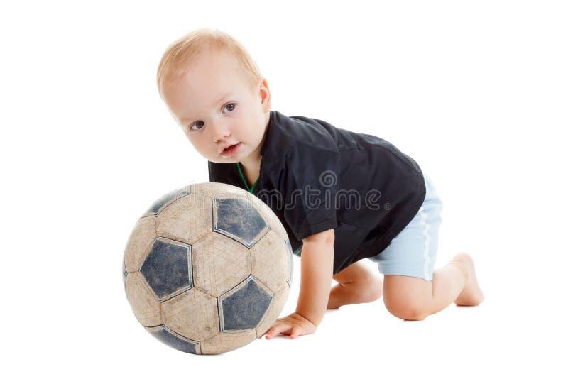 Unge med en fotbollboll Han är jätteglad royaltyfri bild