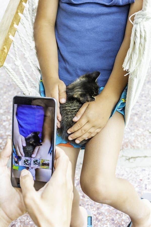 Unge med kattmodern som tar bilden royaltyfria bilder
