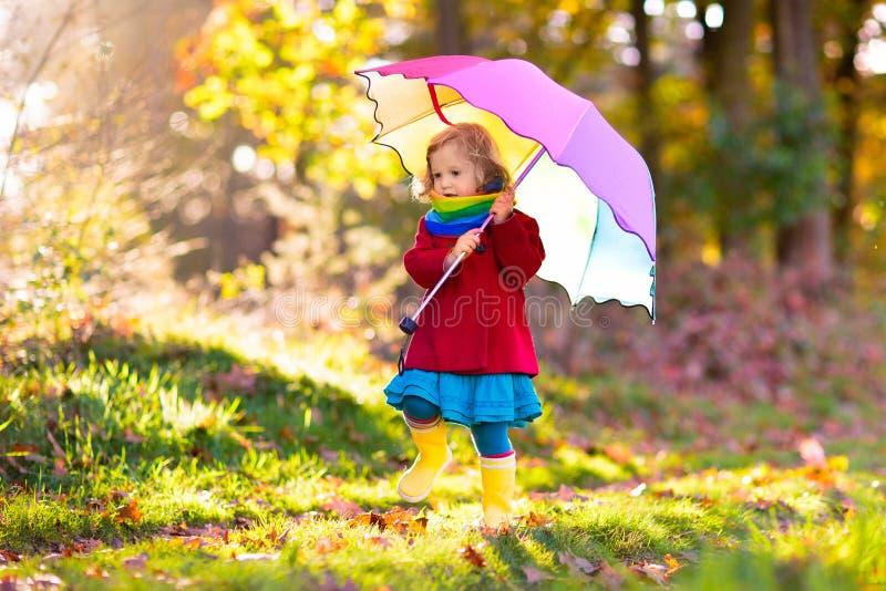 Unge med paraplyet som spelar i höstregn royaltyfri fotografi