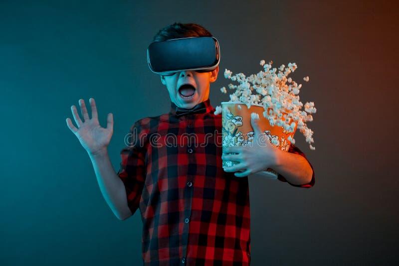 Unge med VR-hörlurar med mikrofon och popcorn royaltyfri foto