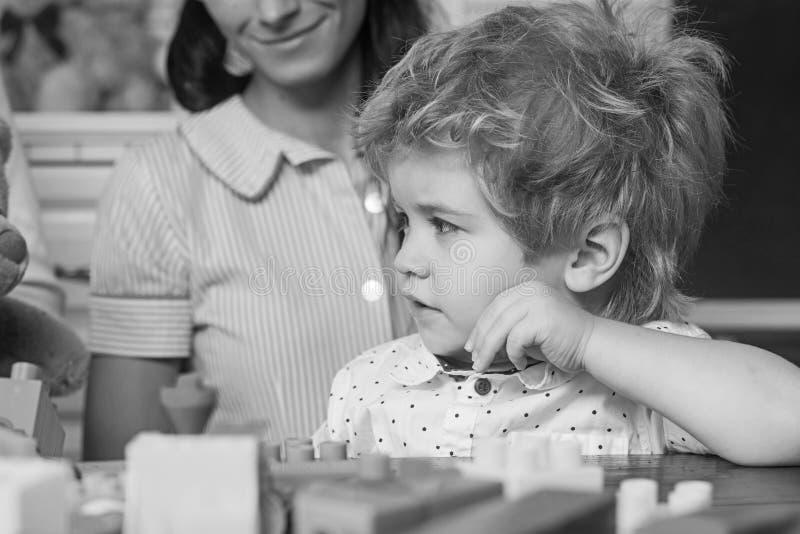 Unge nära färgrika plast- tegelstenar Pojke i lekrum med kvinnan royaltyfria bilder