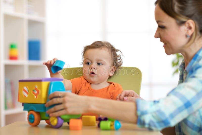 Unge och kvinna som spelar med pusselleksaken i daycare eller dagis royaltyfri bild