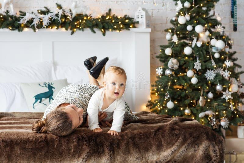 Unge och moder nära ny-år träd fotografering för bildbyråer