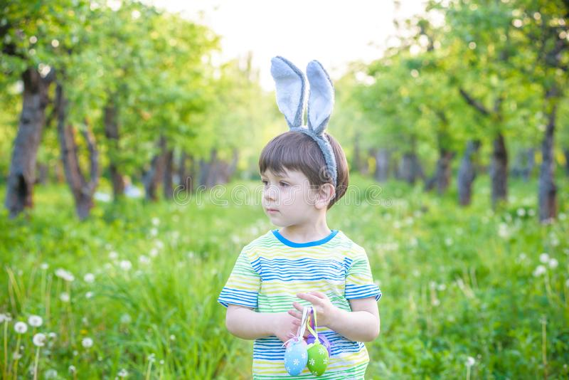 Unge på jakt för påskägg i blommande vårträdgård pojke som söker för färgrika ägg i blommaäng arkivfoto