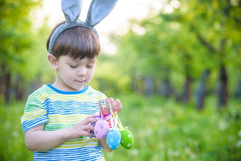 Unge på jakt för påskägg i blommande vårträdgård pojke som söker för färgrika ägg i blommaäng royaltyfri foto