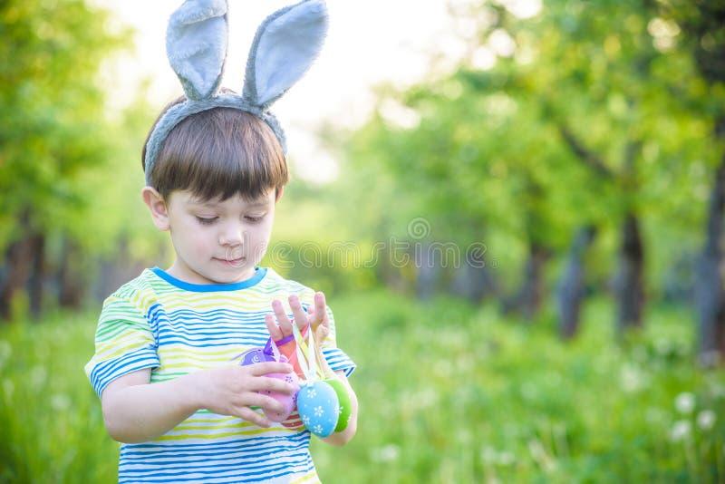 Unge på jakt för påskägg i blommande vårträdgård pojke som söker för färgrika ägg i blommaäng arkivbilder