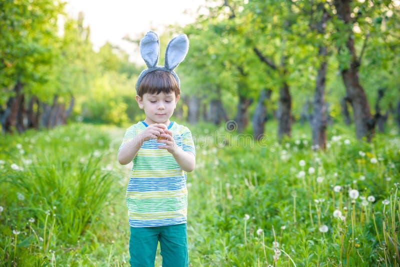 Unge på jakt för påskägg i blommande vårträdgård pojkesökande royaltyfria bilder