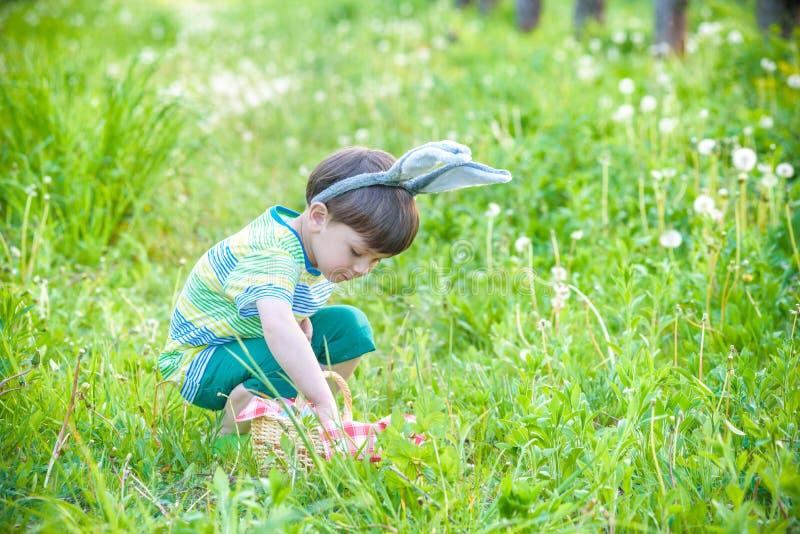 Unge på jakt för påskägg i blommande vårträdgård pojkesökande arkivfoton