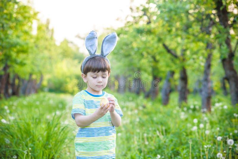 Unge på jakt för påskägg i blommande vårträdgård pojkesökande royaltyfri fotografi