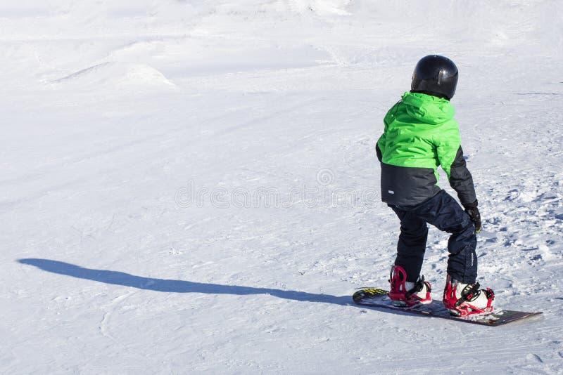 Unge på snowboard i vintersolnedgångnatur Sportfoto med att redigera utrymme arkivbild