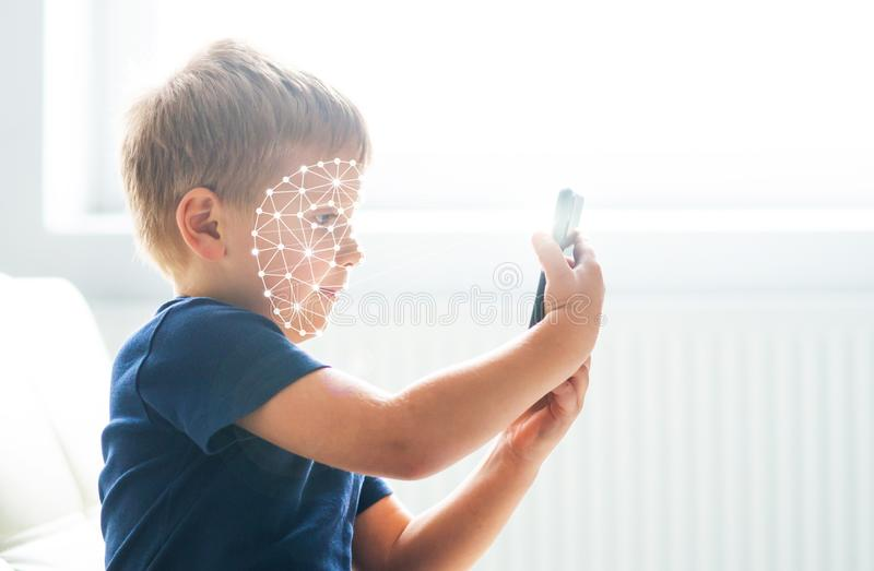Unge som använder framsidaID-erkännande Pojke med en smartphonegrej Digital infött barnbegrepp royaltyfri foto