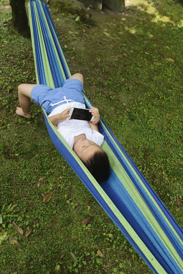 Unge som använder smartphonen på hängmattan royaltyfri bild