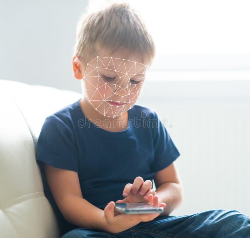 Unge som anv?nder framsidaID-erk?nnande Pojke med en smartphonegrej Digital inf?tt barnbegrepp royaltyfri bild