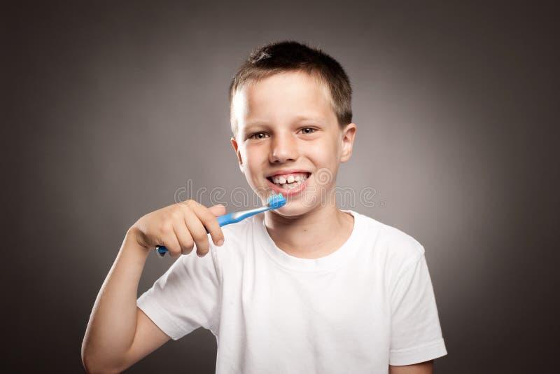 Unge som borstar hans tänder royaltyfri fotografi