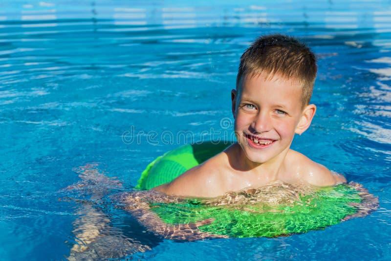 Unge som har gyckel i simbassängen på den uppblåsbara cirkeln Gyckel för sommarsemester royaltyfri foto