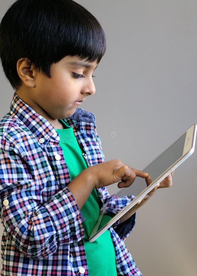 Unge som knackar lätt på på minnestavladatoren Barn som använder tableten arkivfoto