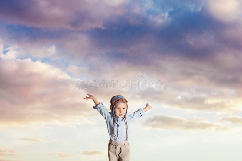 Unge som låtsar flyg på en bakgrund för molnig himmel arkivbild